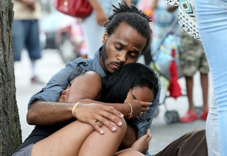 Una pareja yace en el piso, luego de que desconocidos dispararan contra un grupo numeroso de gentes -entre las que estaba la pareja- que salían de un partido de basquetbol, en el Rochester Boys and Girls Club de Nueva York. (AP)