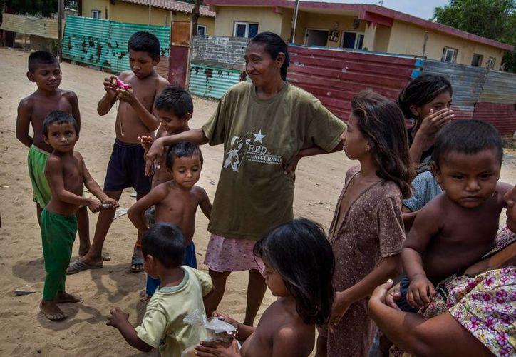 Fotografía de una mujer wayúu con sus hijos en una calle de la localidad de Canchancha en la ciudad de Maracaibo, Venezuela. (EFE)