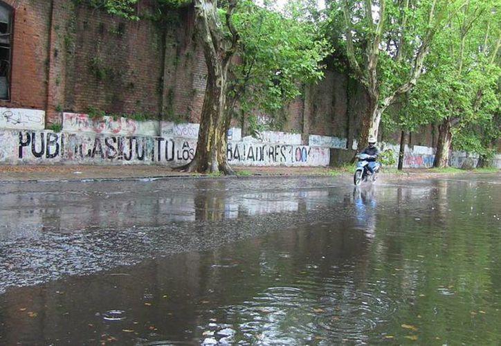 Más de dos mil 300 personas han sido evacuadas en Uruguay por inundaciones. Vehículos cruzan en medio de la lluvia en Montevideo. (EFE)