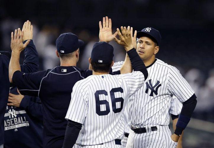 Alex Rodríguez llegó con Yanquis a los 3,000 hits en su carrera. En la imagen, al ser felicitado por sus compañeros de Yanquis luego de conseguir la hazaña. (AP)