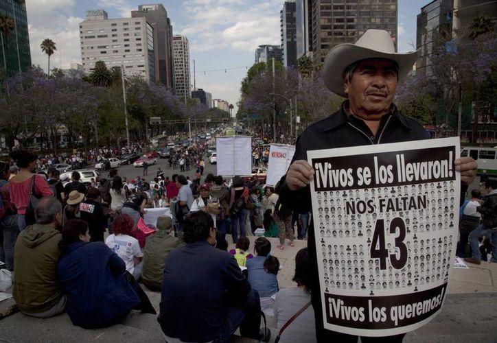 Miembros de la CNTE y la Ceteg participan en la marcha por los jóvenes de Ayotzinapa. (AP)