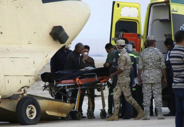 Los trabajadores de emergencia egipcios trasladan los cuerpos de las víctimas del accidente de un avión ruso sobre la península del Sinaí. (Agencias)