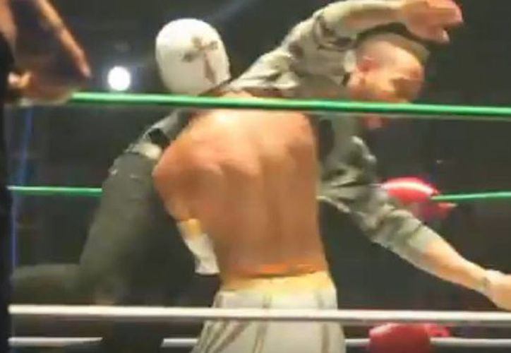 Lewis Hamilton, actual Campeón de Fórmula Uno, se lanza contra Místico, en la Arena México. (Captura de pantalla de YouTube)