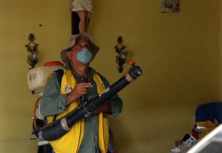 Las acciones de prevención y combate al mosco han evitado que el  zika se propague. Imagen de contexto de un empleado de Salud al momento de fumigar una casa en Mérida. (Milenio Novedades)