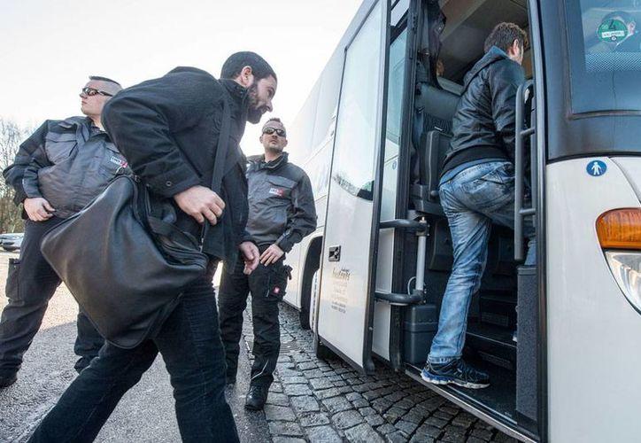 Un grupo de refugiados sirios abordan un autobús en Regenstauf, Alemania, el jueves, 14 de enero de 2016. Según el jefe de Europol, Rob Wainwright, traficantes de personas ganan millones de  dólares en el traslado de inmigrantes en Europa. (Foto archivo/AP)
