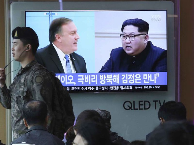A South Korean army soldier passes by a TV screen showing file footage of CIA Director Mike Pompeo, left, and North Korean leader Kim Jong Un during a news program at the Seoul Railway Station in Seoul, South Korea.