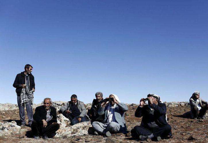 Un grupo de hombres observa una columna de humo que se eleva en la localidad kurdo-siria de Kobani vista desde la frontera en Sanlirufa, Turquía tras un supuesto ataque aéreo de Estados Unidos. (EFE)