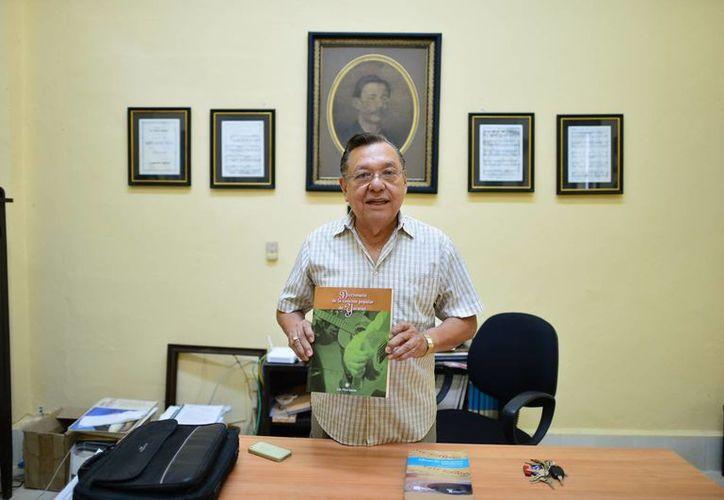 Luis Pérez Sabido al sostener el Diccionario de la Canción Popular de Yucatán. (Luis Pérez/SIPSE)