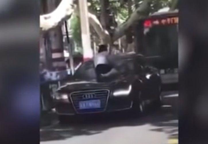 En las imágenes se aprecia un automóvil desplazándose lentamente, mientras una mujer está sentada sobre él, golpeando el parabrisas. (Captura de pantalla RT)