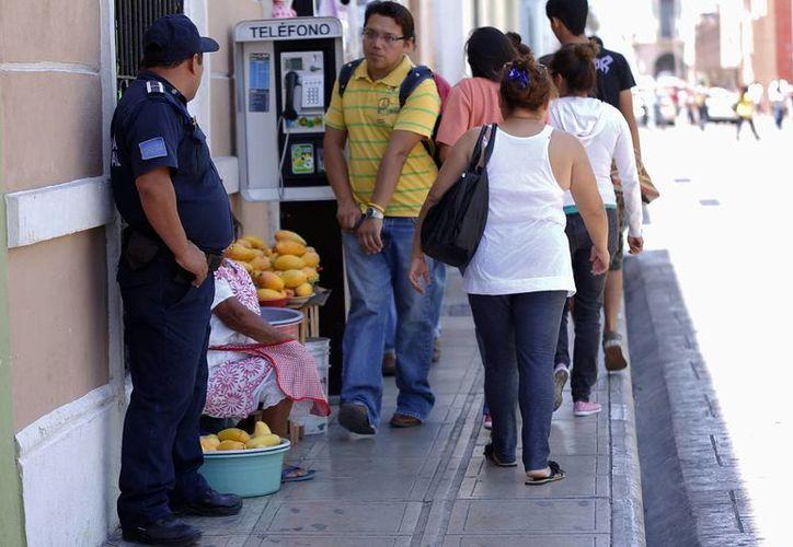 Elemento de seguridad y palanganera, en acera del Centro Histórico. (Juan Albornoz/SIPSE)