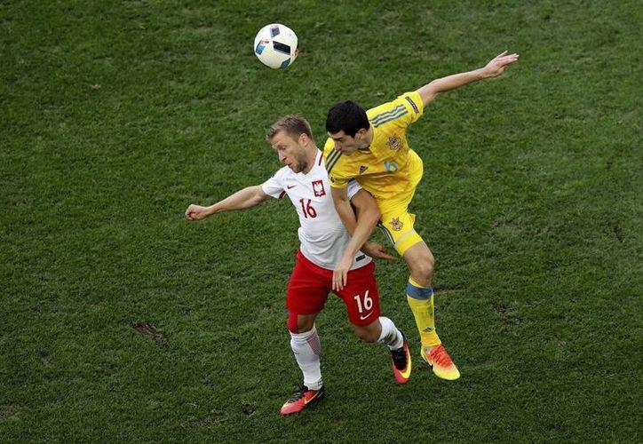 El jugador polaco Jakub Blaszczykowski (izq) y el ucraniano Taras Stepanenko en una jugada durante partido de fútbol del Grupo C, de la Euro 2016, entre Ucrania y Polonia en el estadio Velódromo de Marsella, Francia. (Foto AP / Claude Paris)