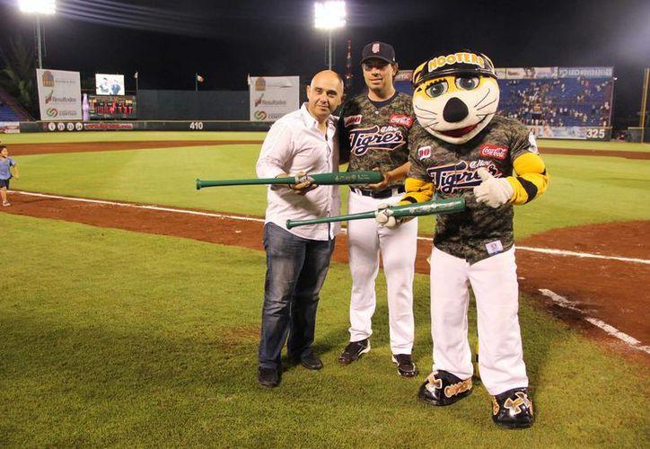 """Jorge Morales recibió de Pablo Ortega  y la mascota """"Chacho"""" los bates. (Cortesía/SIPSE)"""