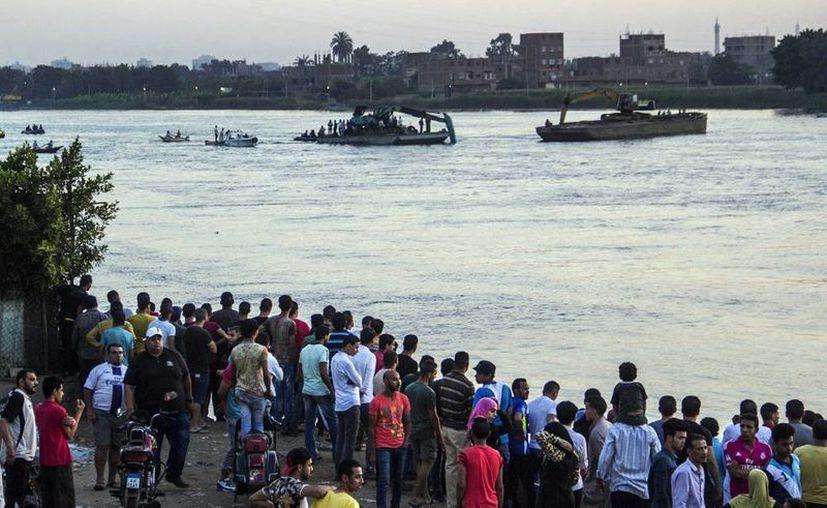 Un grupo de egipcios acude al lugar donde se produjo el hundimiento de un barco en el río Nilo ayer, en Egipto. (EFE)