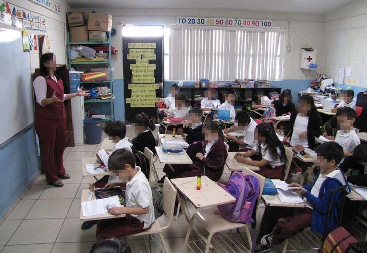En los reglamentos de las escuelas se da una escasa mención al descanso necesario de los niños y la importancia de dormir y comer bien. Imagen de una maestra dando clases en un salón. (Archivo/Agencias)