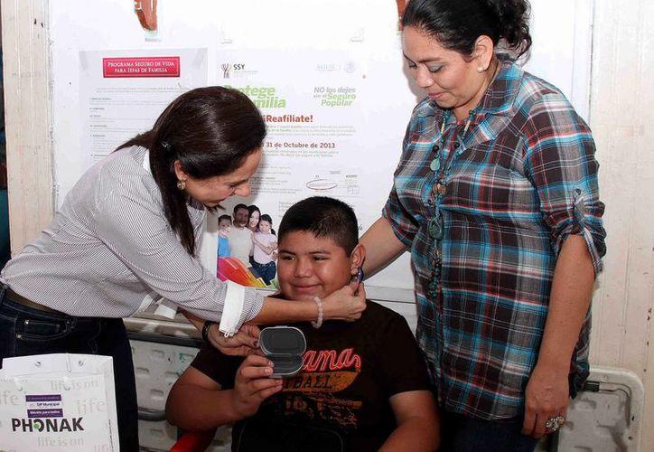 La presidenta del DIF Mérida, Diana Castillo Laviada de Barrera, coloca el aparato auditivo a Leonel Arturo Mendoza Cutz, quien nació con sordera total. (SIPSE)