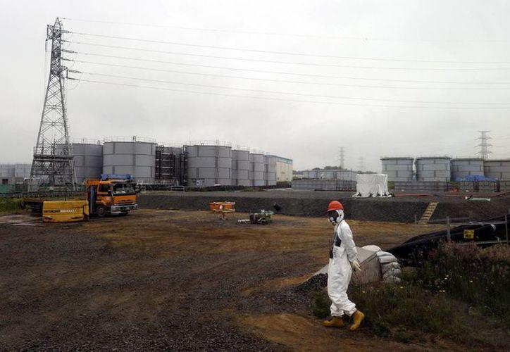 Una imagen de archivo muestra a un trabajador caminando cerca a los tanques de agua el 12 de junio de 2013 en la planta nuclear de Fukushima. (Archivo/EFE)