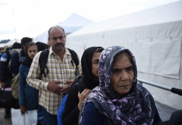 Una mujer afgana y un grupo de personas hacen fila para cruzar de la aldea griega norteña de Idomeni hasta el sur de Macedonia. Muy pocos de los que lleguen en Grecia quieren permanecer en el país afectado financieramente. (Foto AP/Giannis Papanikos)