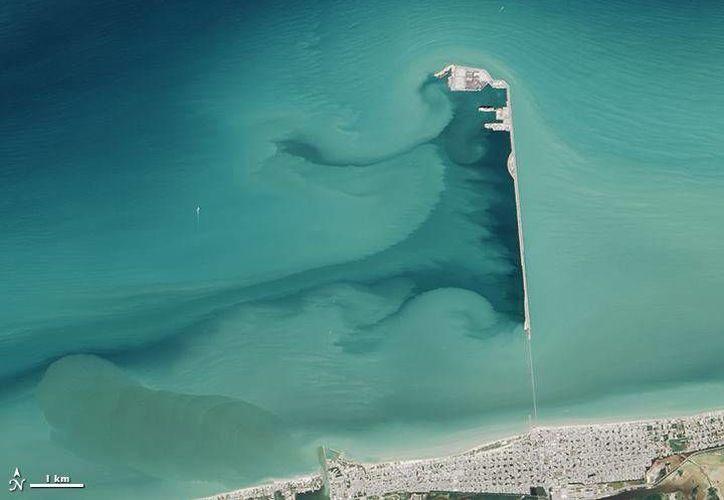 En esta imagen la NASA ejemplifica la erosión costera que ha ocasionado el puerto de altura en Progreso. (Facebook/NASA's Earth Observatory)
