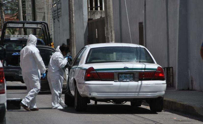 El vehículo fue examinado por los peritos criminalistas. (Redacción/SIPSE)