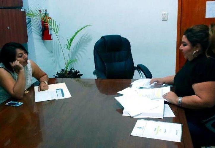 La regidora priista Alejandra Cerón Grajales, derecha, entrega a su colega panista Manuela Cocom Bolio, un oficio en el que solicita una explicación del incumplimiento de compromisos en subcomisarías. (SIPSE)