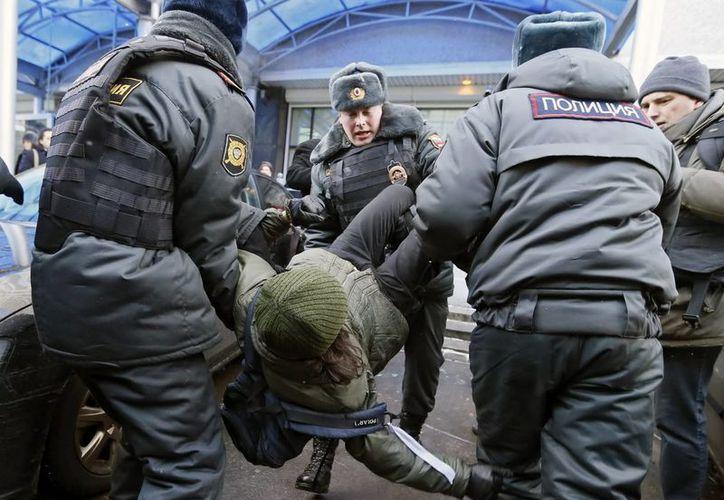 Agentes de policía detienen a una manifestante durante una protesta en favor de los derechos de los homosexuales frente a la Duma. (Archivo/EFE)