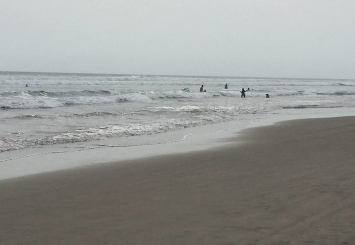Imagen de un grupo de surfistas que aprovechan las olas antes de la llegada de un nuevo mar de fondo. Autoridades piden a la población que extremen las medidas de precaución. (Archivo/Notimex)