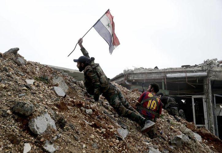 Un soldado del ejército sirio coloca una bandera del país durante una batalla contra combatientes rebeldes en el frente de Ramouseh, en el este de Aleppo, Siria. (AP/Hassan Ammar)