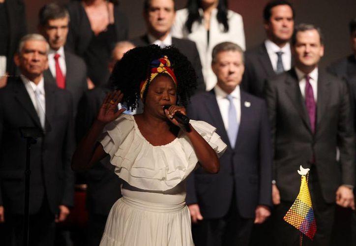 Cecilia Silva Caraballo (frente), cantante del grupo colombiano Tambores del Cabildo, canta el tema 'Violencia' en la ceremonia de la firma del nuevo acuerdo de paz para terminar 52 años de conflicto armado interno entre el presidente de Colombia, Juan Manuel Santos, y el jefe máximo de las FARC Rodrigo Londoño Echeverry hoy, jueves 24 de noviembre de 2016, en Bogotá (Colombia). EFE