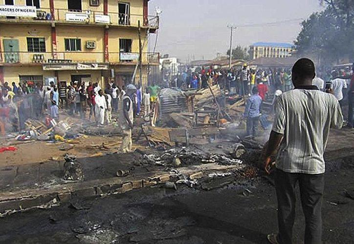 Decenas de personas observan los restos carbonizados de varios vehículos tras una explosión en la ciudad de Kaduna, en el norte de Nigeria. (EFE/Archivo)