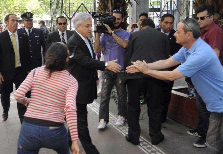 Momento en el que la mujer le escupe al presidente de Chile, Sebastián Piñera. (twitter.com/chilevision)