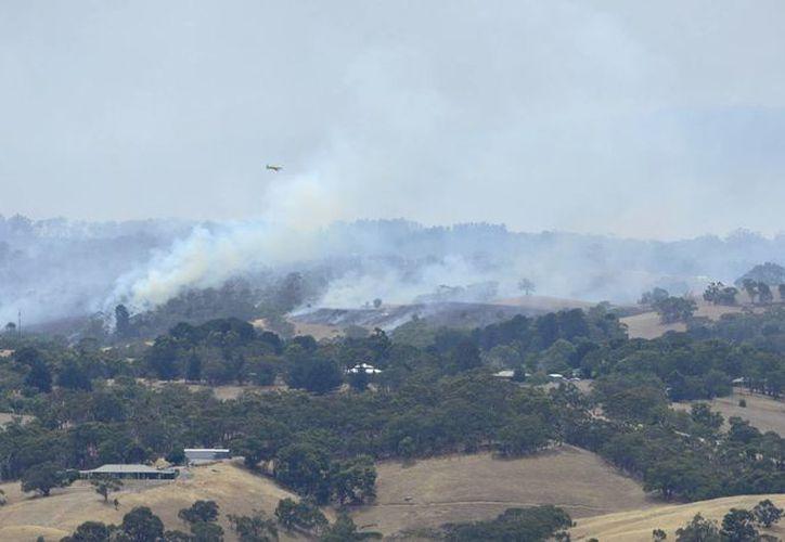 Vista panorámica de un gran incendio desatado en las colinas de Adelaida, Australia, lo cual ha obligado a los residentes de 19 ciudades de la zona a buscar refugio fuera de sus casas. (EFE)