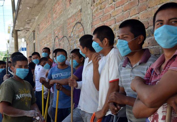 Los más recientes huracanes derivaron en inundaciones y estas a los brotes de cólera en el país. En la foto, jóvenes se disponen a hacer labores de limpieza. (Notimex)