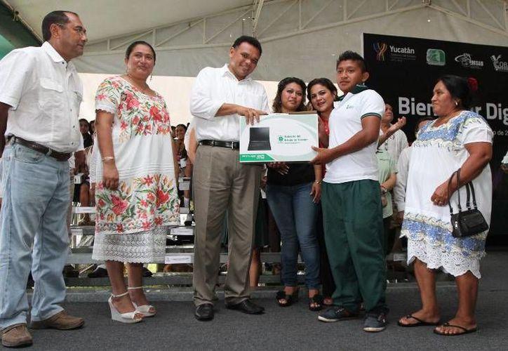 El gobernador Rolando Zapata Bello entrega una computadora a un estudiante de Sotuta. (SIPSE)