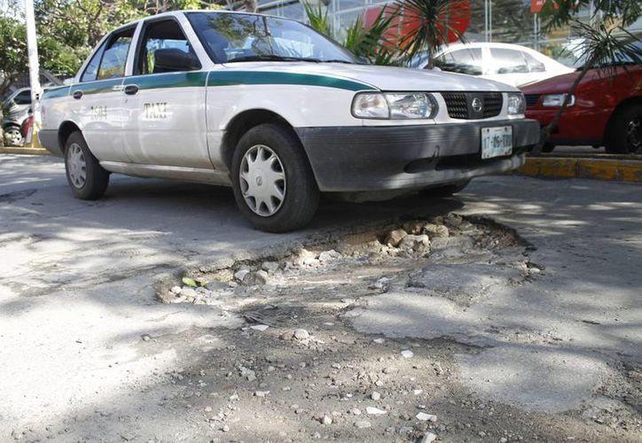 Después de las precipitaciones pluviales, personal de Obras Públicas cubre las partes dañas con chapopote. (Yajahira Valtierra/SIPSE)
