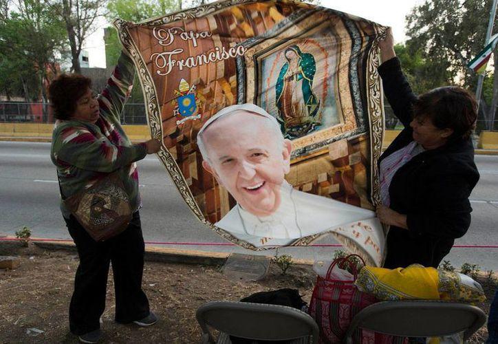 Dos mujeres despliegan un poster con imágenes del Papa Francisco y la Virgen de Guadalupe, cerca de la Nunciatura donde el Pontífice pasó su primera noche en México. (Foto: AP/Moisés Castillo)