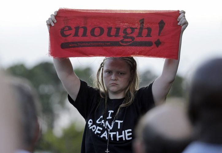 """Un adolescente sostiene una pancarta con la palabra """"¡basta!"""" en una marcha contra la muerte de Walter Scott a manos de un agente de policía en North Charleston. (Agencias)"""