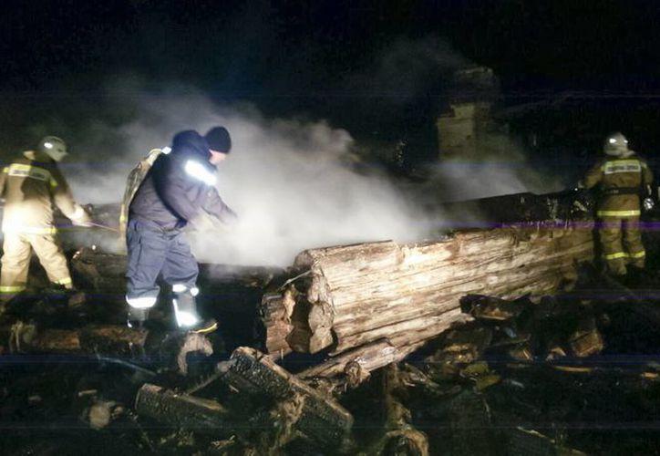 En esta foto proporcionada por el Ministerio de Situaciones de Emergencia de Rusia, bomberos intenta extinguir un incendio en una casa de madera en la región Leningorsk de Tatarstan, Rusia. (Agencias)