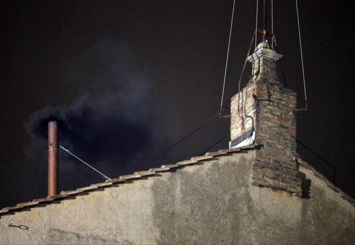 El humo negro sale de la chimenea en el techo de la Capilla Sixtina, en la Plaza de San Pedro en el Vaticano. (Agencias)