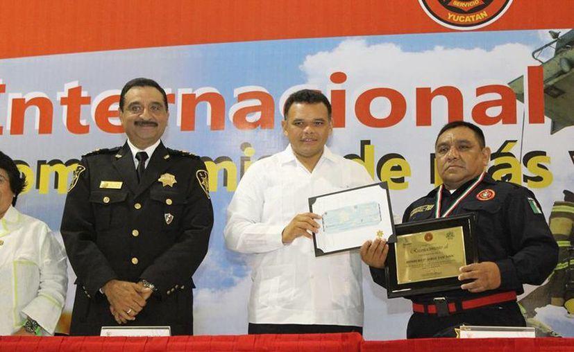 Jorge Yam Xooc (d) recibió de manos del gobernador Rolando Zapata  un reconocimiento como el Bombero del Año. (SIPSE)