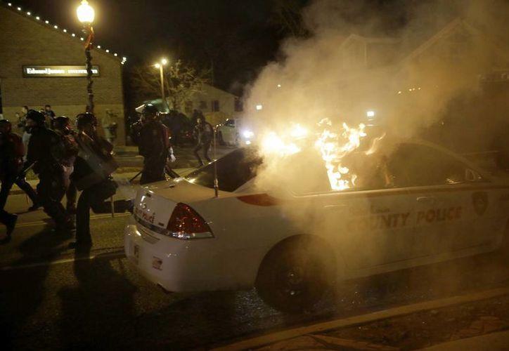 Un vehículo de la policía arde en una calle de Ferguson, tras el ataque de manifestantes enojados por el fallo que dio un jurado de no acusar a un policía que mató a un joven negro. (AP Photo/David Goldman)