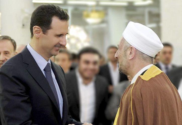 Bachar Asad saludando al presidente de la Federación de Científicos Levant, Mohamed Tawfik Ramadan Buti, tras los rezos. (EFE)