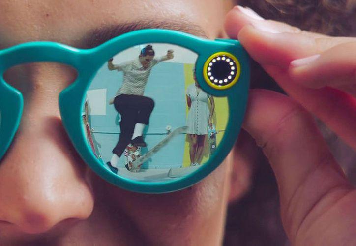 """La compañía Snap, responsable de la aplicación Snapchat, lanzó la nueva versión de Spectacles, unos lentes que incorporan una cámara inalámbrica capaz de tomar fotos, grabar videos y ahora también de resistir al agua.  En setiembre del 2016, la compañía lanzó al mercado la primera versión de las gafas. En aquel momento, solo tenían la capacidad de grabar videos circulares de menos de 30 segundos y transmitirlos de forma inalámbrica a la aplicación social.  Estas son las nuevas gafas de Snap. Estas son las nuevas gafas de Snap. El formato de grabación de los videos sigue siendo circular en HD y funciona así: para capturar 10 segundos, se debe oprimir el botón una vez; si el usuario quiere permanecer grabando hasta 30 segundos, entonces deberá presionarlo de nuevo y, finalmente, si quiere tomar una foto, entonces tendrá que oprimirlo de forma continuada.   """"Los Spectacles están diseñados para sobrevivir a fiestas en la piscina y días lluviosos, ¡e incluso pueden tomar una foto o un video en aguas poco profundas!"""", asegura la compañía en la página promocional de las gafas, que cuestan $150, unos ¢84.000.  El dueño de estos lentes podrá grabar unos 70 videos, que es lo que rinde una sola carga.  LEA TAMBIÉN Snapchat anuncia sus gafas Spectacles con cámara incorporada  Además, cuando el teléfono está cerca, Spectacles logra sincronizarse de forma inalámbrica con Snapchat. Luego, la persona puede compartir sus momentos favoritos con amigos, o bien exportarlos a la galería de fotos de sus dispositivos.  ¿Qué se requiere para poder usarlos? Tener la aplicación Snapchat instalada en un iPhone 5 o posterior con el sistema operativo iOS 10 o superior, o bien, un teléfono Android con la versión del sistema operativo Android 4.4 o superior, con Wi-Fi Direct y Bluetooth Low Energy (BLE).  Las gafas se conectan al teléfono por medio de Bluetooth y tienen una capacidad de almacenamiento de 4 GB.  El dispositivo se lanzó esta semana en Estados Unidos, Reino Unido, Canadá y Francia, """