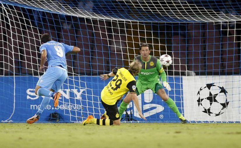 Tras su salida del Real Madrid, 'Pipita' mantiene la mecha encendida con el Nápoles. En la foto anota su gol contra el Borussia. (Agencias)
