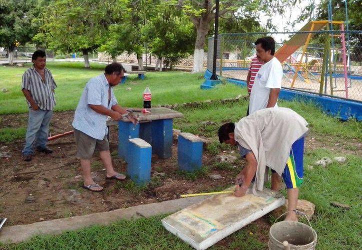 Vecinos de Opichén reparan las bancas del parque. (SIPSE)