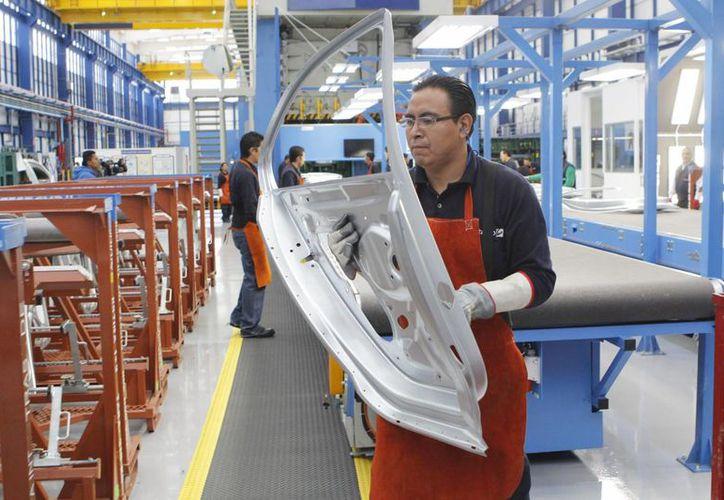 En octubre pasado se tuvo el mayor aumento de empleo formal, según el IMSS. Imagen de obreros en la planta Gestamp que fabrica autopartes, en Puebla. (Foto Archivo/Notimex)