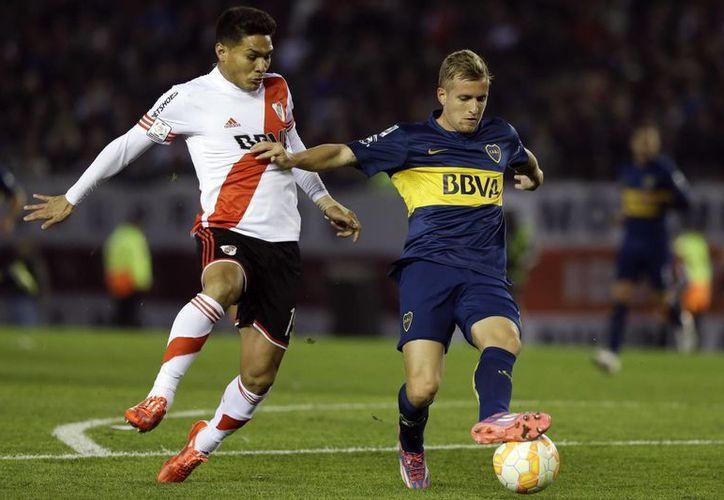 Téofilo Gutiérrez, de River Plate, y Nicolas Colazo, de Boca Juniors, disputan el balón en partido de octavos de final de Copa Libertadores que finalmente fue suspendido. (Foto: AP)
