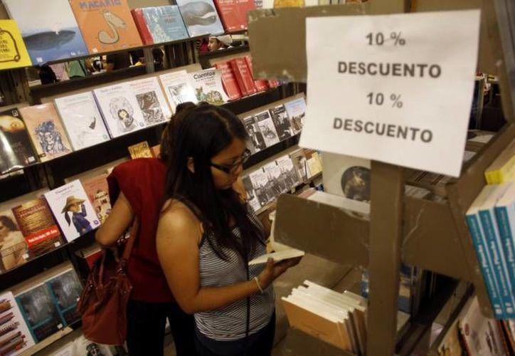 En la  Feria Internacional de la Lectura Yucatán promueven la creación literaria de escritores mexicanos. En la imagen, una joven mira un libro en la Filey del año pasado. (Milenio Novedades)