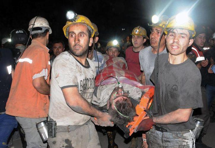 Mineros llevan un compañero herido después de una explosión e incendio en una mina de carbón en Soma, Turquía. (Agencias)