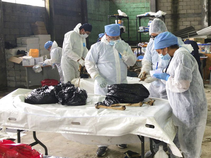 Forensic workers examine the remains of a victim of the Volcan de Fuego eruption.
