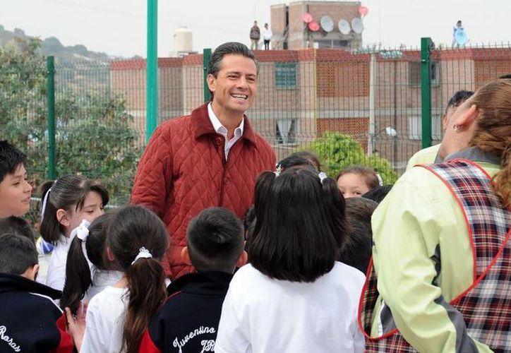 Peña Nieto conviviendo con familias ayer en Puebla. (presidencia.gob.mx)